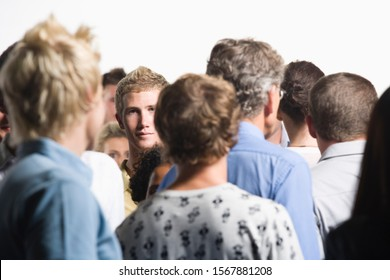 Businessman staring out from crowd of co-workers