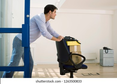 Businessman in start up company wheeling chair into empty office with no furniture