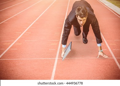 Businessman in the starting blocks holding laptop against focus of athletics track