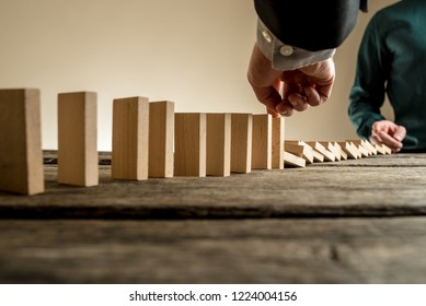 Businessman starting domino effect by collapsing the first domino with his finger and the other entrepreneur stopping the dominos from collapsing completely.