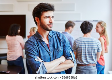 Businessman in start-up company thinking with crossed arms