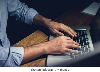 Businessman staying overtime late at night in the office focusing on working with laptop computer at his desk