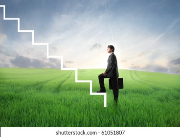 Businessman stepping up the stairs from a green meadow