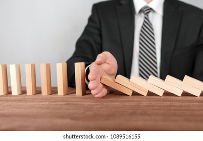 Businessman stopping domino effect with his hand. Security and insurance concept