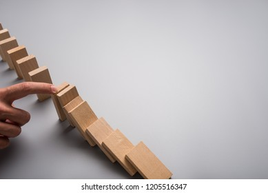 Businessman stopping domino effect with his finger on grey background with copy space.