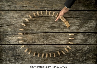 Businessman stopping falling dominos placed in a circle with his hand. Conceptual of crisis and problem management.