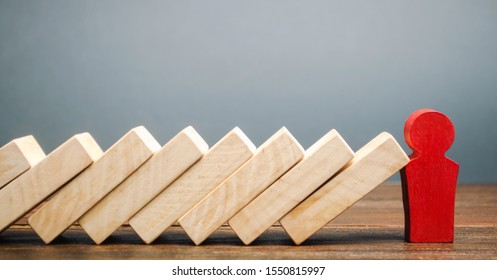 Businessman stops domino falling. Risk management concept. Successful strong business and problem solving. Reliable leader. Stop the destructive processes. Strategy development. Debt restructuring