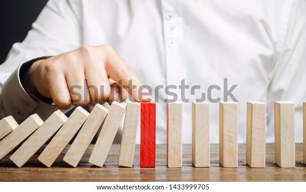 El hombre de negocios detiene la caída de dominó. Concepto de gestión de riesgos. Éxito en la resolución de problemas y negocios. Líder confiable. Detengan los procesos destructivos. Elaboración de estrategias. Reestructuración de la deuda