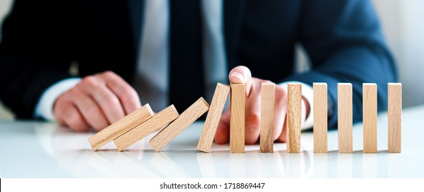 businessman stops falling wooden blocks. business solutions concept