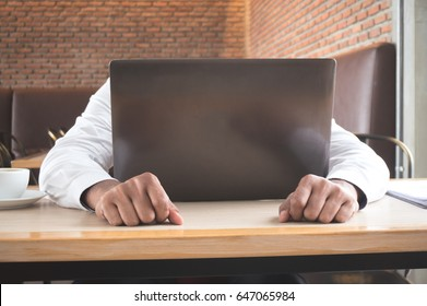 Businessman stress and fall down on table with laptop in coffee shop