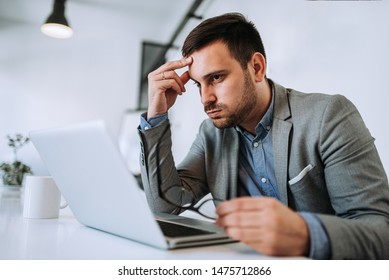 Businessman stressed out in the office looking at the computer.