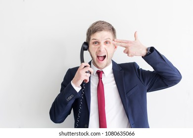 Businessman stressed out at work using the phone very exchausted ready to shoot himself.