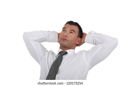 Businessman stretching his arms behind his head