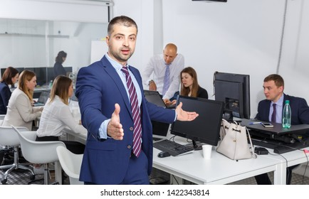 Businessman stretching open hand offering handshake and inviting to cooperation in modern office
