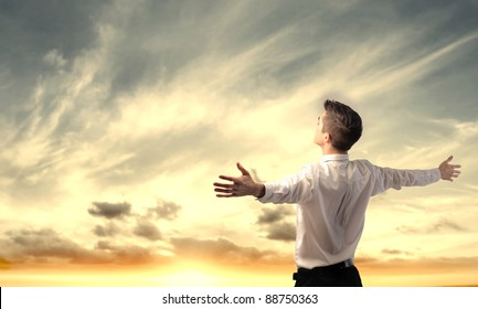 Businessman stretching out his arms in front of a sunrise