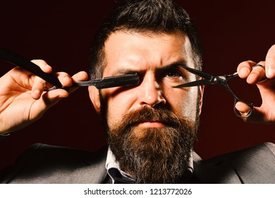 Businessman with strict face on dark red background. Man with beard holds razor and scissors in front of eyes. Macho in formal suit cuts and shaves beard and moustache. Business and barbershop concept
