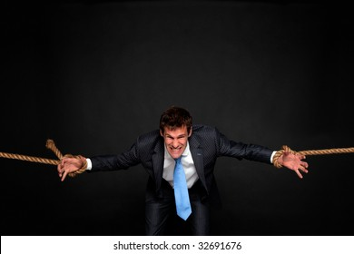 Businessman struggling as he's pulled by rope attached to his wrists on both sides, dark background.