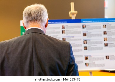 Businessman studies presentation. An older the shoulder view of an older businessman viewing a presentation during a workplace conference. Man contemplates information on display board