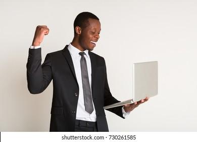 Businessman in stylish suit, tie standing, holding laptop at hands. Portrait. Winner concept, copy space