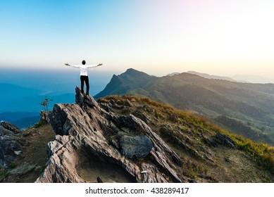 businessman success hiking on the peak of rocks mountain at sunset, winner leader concept
