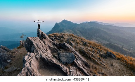 businessman success hiking on the peak of rocks mountain at sunset, winner leader concept