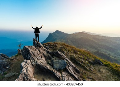 businessman success hiking on the peak of rocks mountain at sunset
