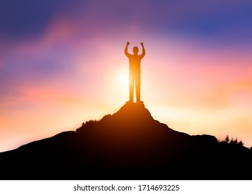 Businessman success or winner on top peak of rocks mountain at sunset, leader concept, Rear view of businessman with suitcase looking at sunset winner moment
