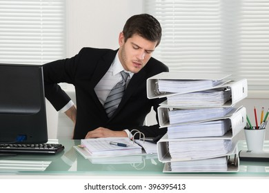 Businessman Suffering From Back Pain With Invoice On Desk