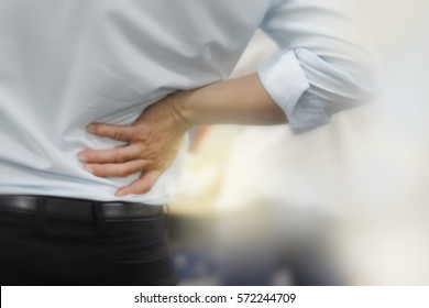 Businessman suffering from back and waist pain at office, office syndrome.
