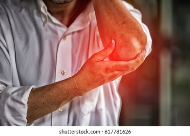 Businessman suffering from elbow pain at office High Dynamic Range tone