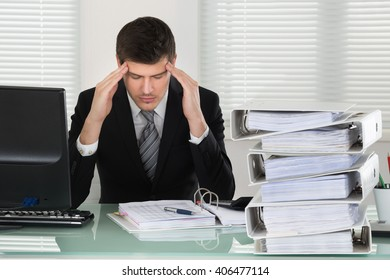 Businessman Suffering From Headache With Invoice On Desk