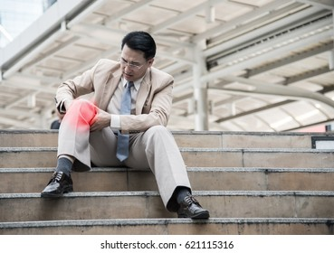 Businessman Suffering from knee Pain sitting on stair, pain and injury concept.