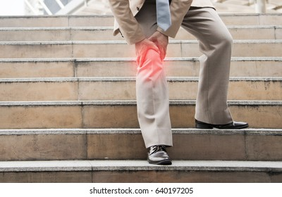 Businessman Suffering from knee Pain sitting on stair