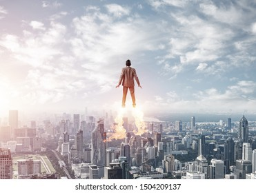 Businessman in suit and aviator hat flying in blue sky as superhero. Back view of corporate manager as superman launching upwards with jet flame above modern city. Successful business startup