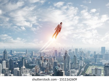 Businessman in suit and aviator hat flying in blue sky as superhero. Corporate manager as superman launching upwards with jet flame above modern city. Successful business startup motivation concept