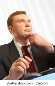 The businessman in a suit behind a table, with a ball pen in hands.