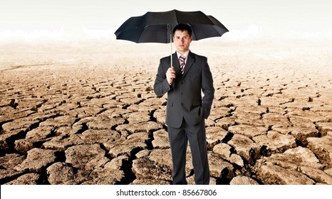 Businessman in suit with black umbrella in a desert