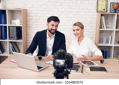 Businessman in suit and businesswoman in blouse discussing for business podcast.