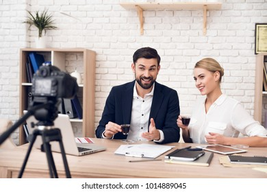 Businessman in suit and businesswoman in blouse drinking coffee for business podcast.