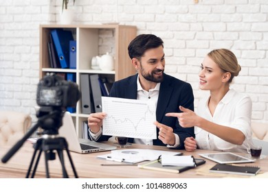 Businessman in suit and businesswoman in blouse showing charts for business podcast.