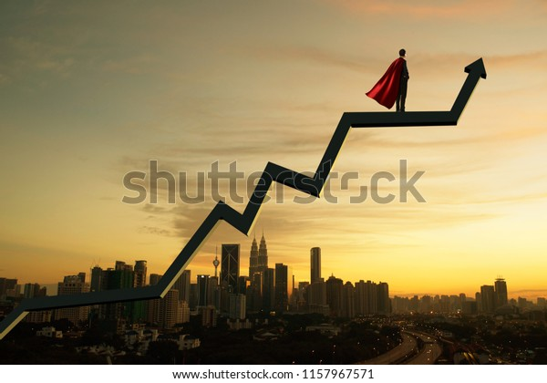 Businessman in suit and cape hero and charts with sunrise city skyline background . Financial economic growth concept