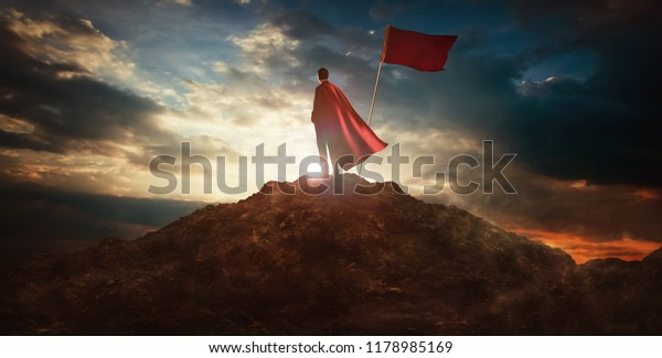 Businessman in a suit and cape hero on top of a mountain,Business Success concept.