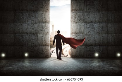 Businessman in a suit and cape stand on stair against concrete wall with huge door ,sunrise scene city skyline outdoor view .