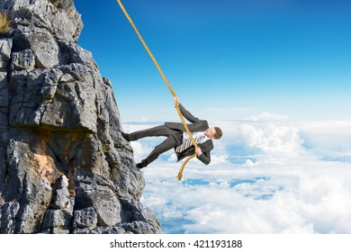 Businessman in suit climbing on mountain with rope