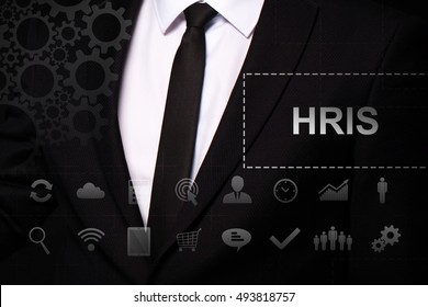 "Businessman in the suit close. Text ""HRIS"" on the virtual screen badge, on the chest. Business concept. Internet concept."