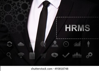 "Businessman in the suit close. Text ""HRMS"" on the virtual screen badge, on the chest. Business concept. Internet concept."