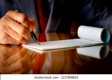 Businessman in suit cloth with necktie, hand writing and signing check book on the wooden table at modern office. Paycheck concept. Payment by cheque. Copyspace with reflection.