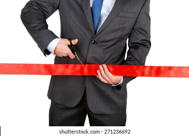 Businessman in suit cutting red ribbon with pair of scissors isolated on white background. Grand opening concept. Traditional public festive ceremony.