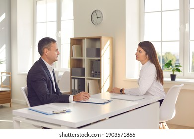 Businessman in suit discussing project with woman office worker manager or interviewing candidate for vacancy in office of modern company. Working in office, meeting, interview concept