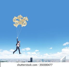 businessman in a suit flying happily holding three balloons in shape of dollars over new york, bright blue sky, concept of success and career growth